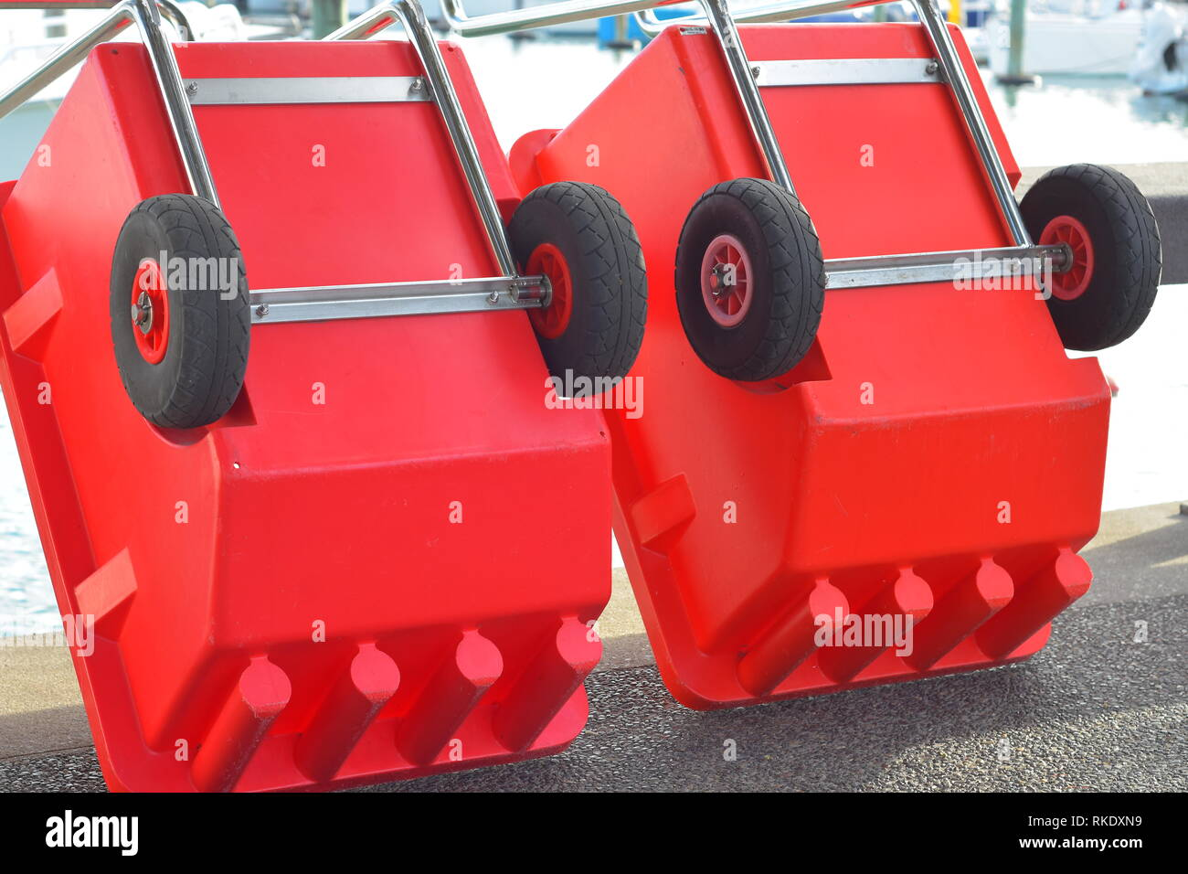 Red plastic box shaped industrial trolleys with one axle and galvanized metal frame and handle. - Stock Image