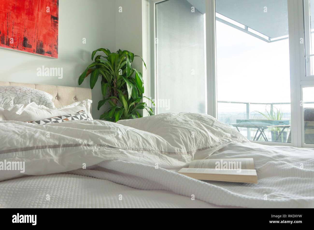 Book on wrinkled, used bed with wall art in a bright apartment or vrbo, bedroom with tall windows and window light. Depicting a staycation, relaxing. - Stock Image