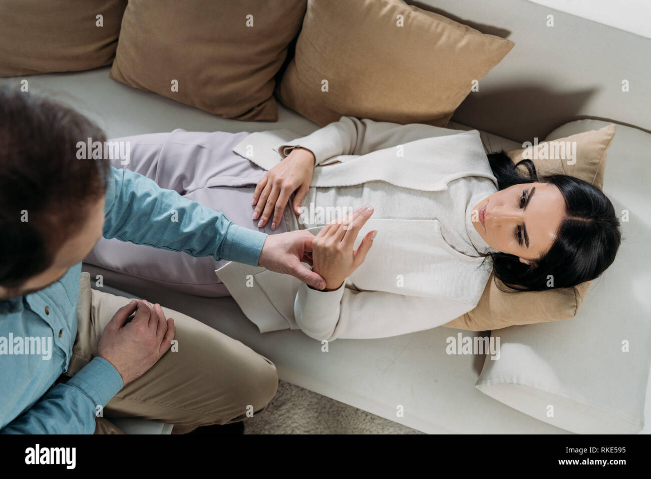 overhead view of hypnotist holding wrist of young woman lying in couch - Stock Image
