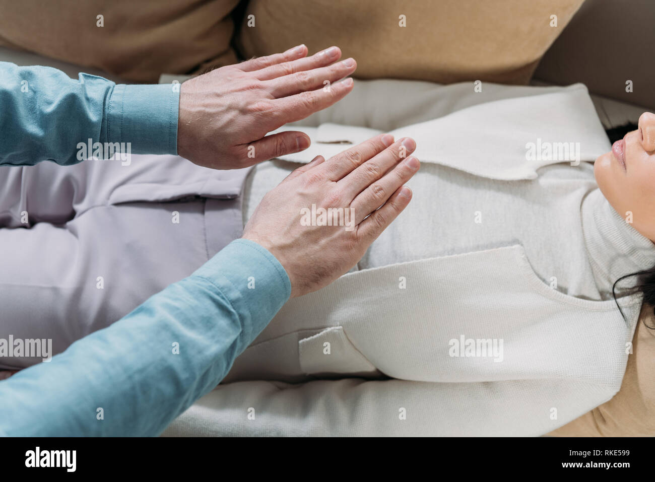 cropped shot of man doing reiki healing therapy to young woman lying on couch - Stock Image