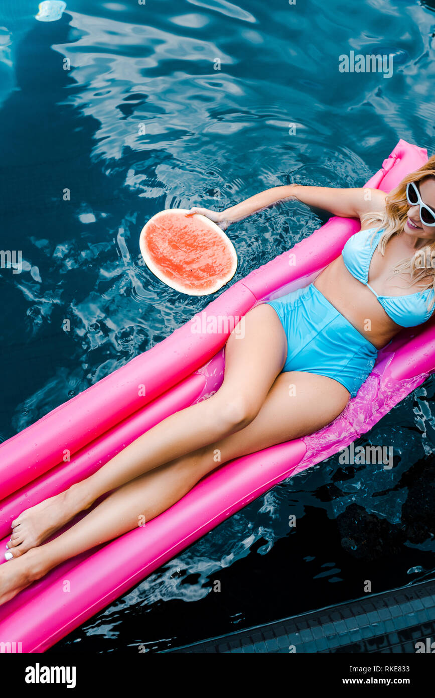 3a52945d840d6 beautiful girl in swimsuit resting on pink inflatable mattress in swimming  pool - Stock Image