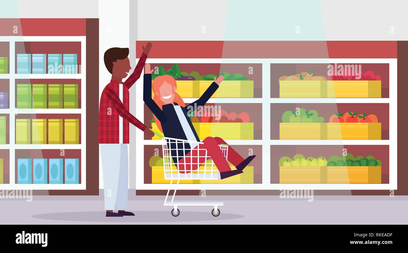 man carrying trolley cart with woman happy mix race couple having fun supermarket interior shopping concept male female cartoon characters full length - Stock Vector