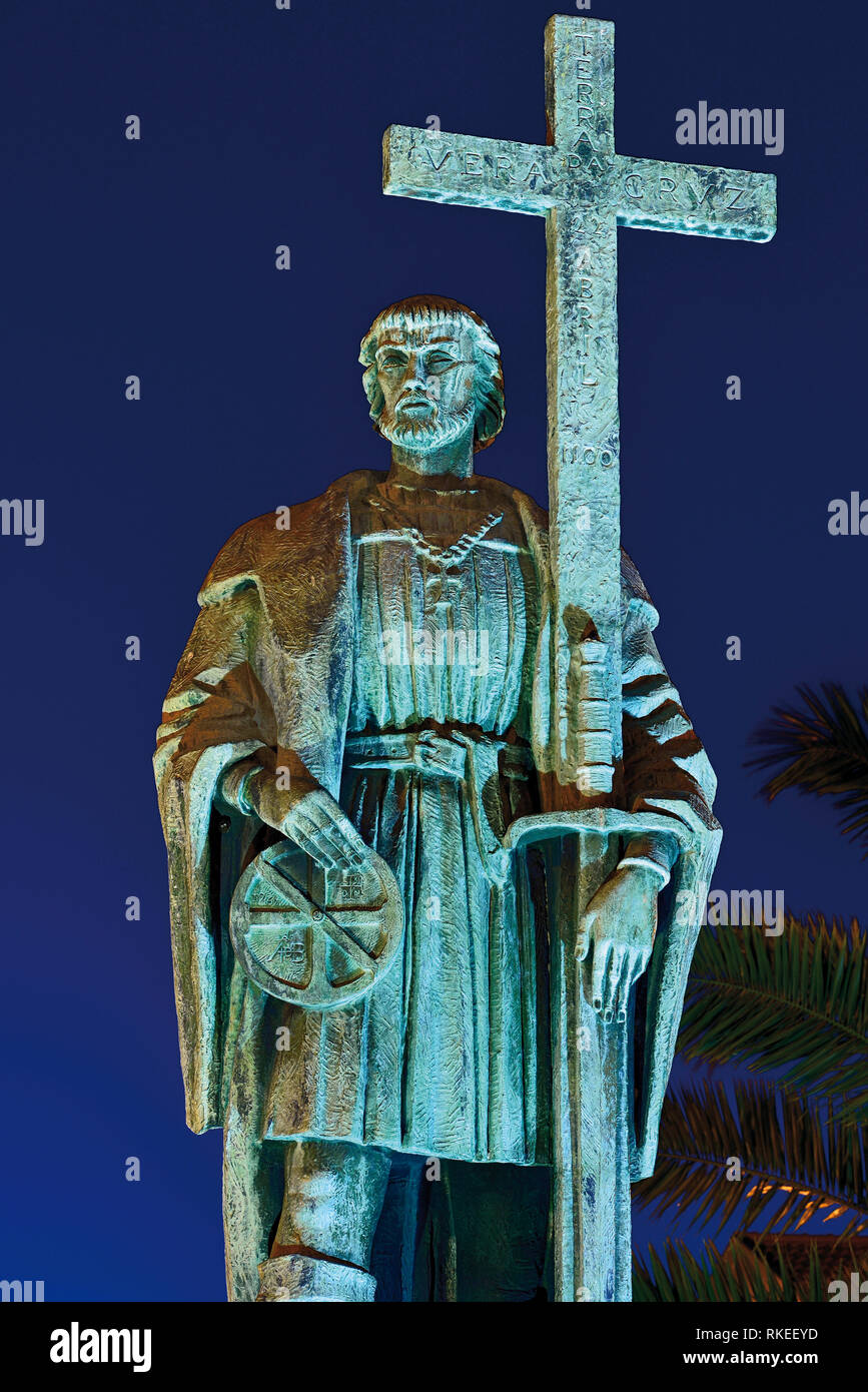 Nocturnal illuminated statue of medieval navigator with cross - Stock Image