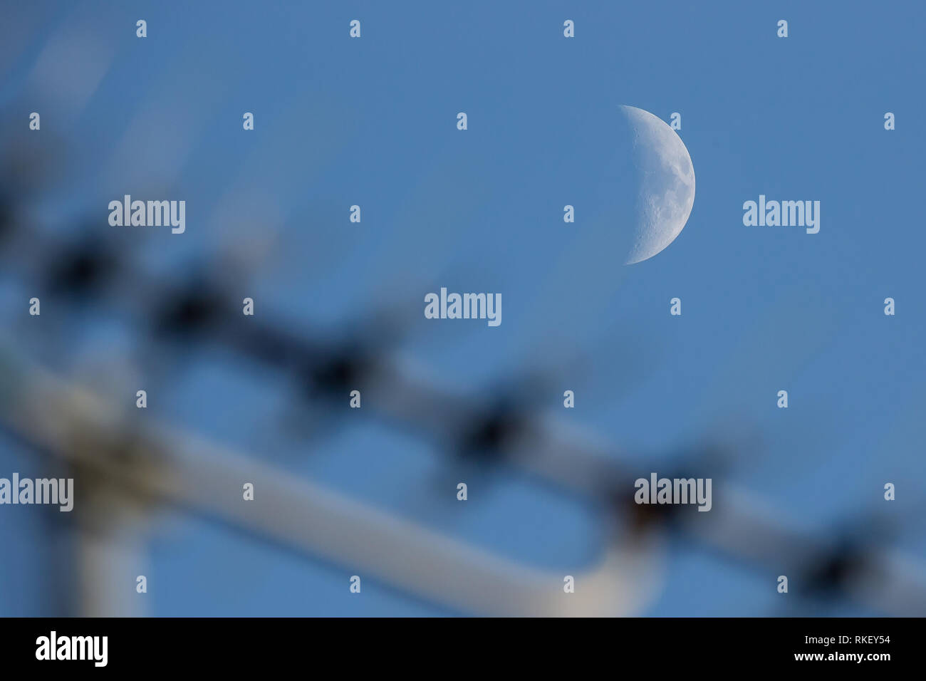 Kidderminster, UK, 11th February, 2019. UK weather: almost clear blue skies reveal a waxing crescent moon as the day draws to an end. It will be a chilly night with temperatures not rising above 2 degrees celsius. The moon can be seen rising above the television aerial on a house roof. Credit: Lee Hudson/Alamy Live News - Stock Image