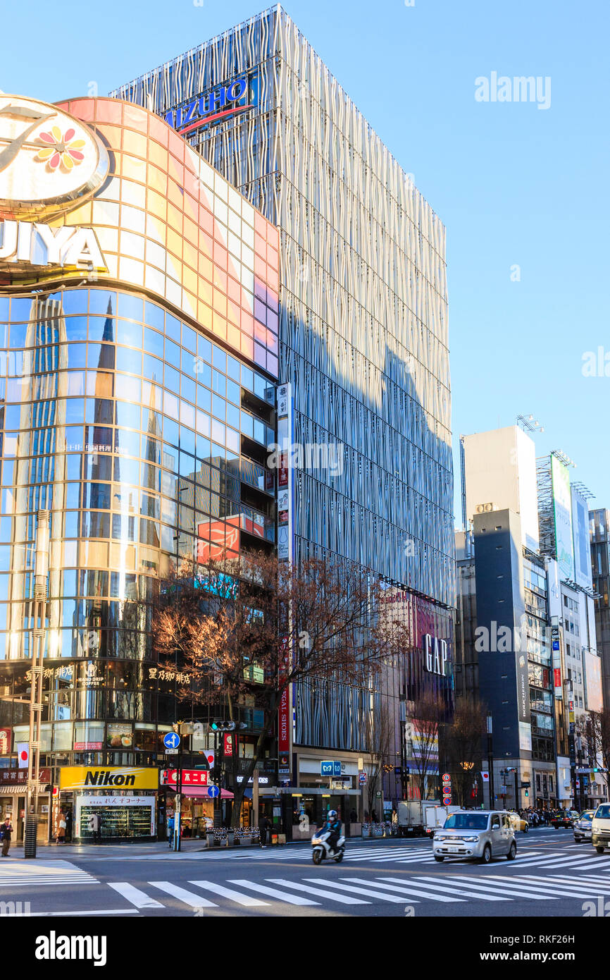 Tokyo, Ginza, golden hour. Flagship 4 level Gap store, largest in Japan, on Chuo Dori shopping street. Foreground, pedestrian crossing. Stock Photo
