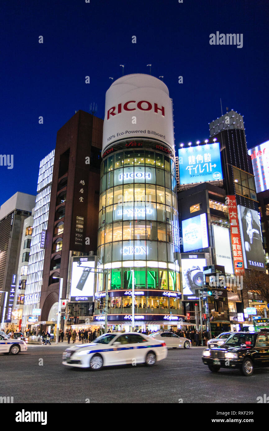 Tokyo, Ginza, night. 4-chome intersection, cars passing, with glass fronted San-ai Building, aka as the Ricoh building with its famous billboard. - Stock Image