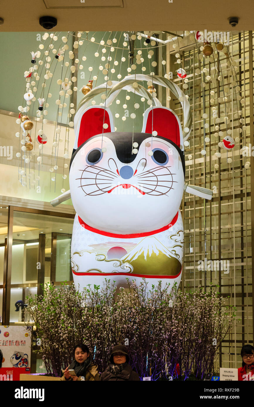 Tokyo, Ginza. Two mature Japanese women sitting in front of giant inflated lucky cat inside entrance lobby of luxury store by shopping advisor counter - Stock Image