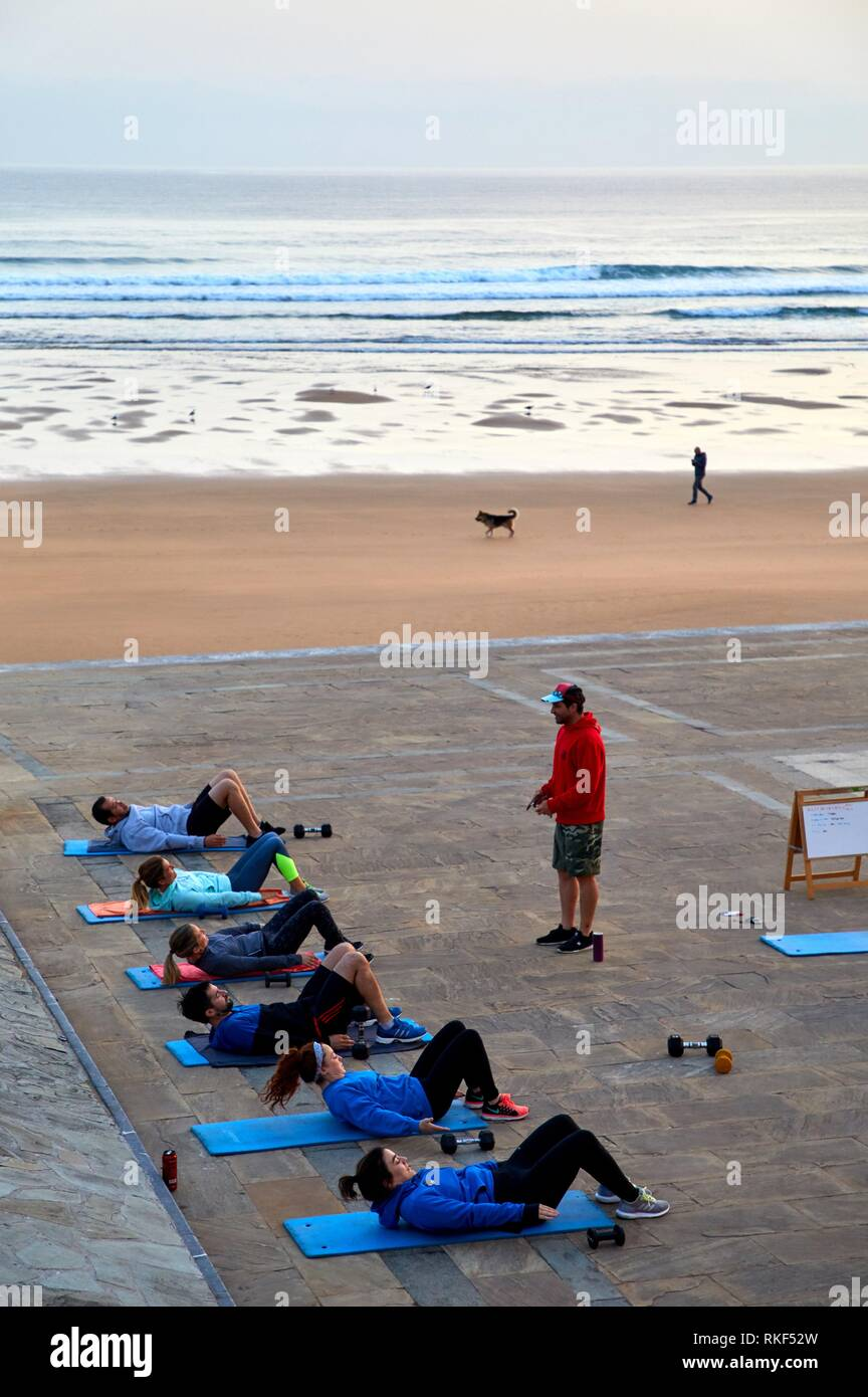 Gymnastics at sunrise on the beach, Zarautz, Gipuzkoa, Basque Country, Spain, Europe - Stock Image