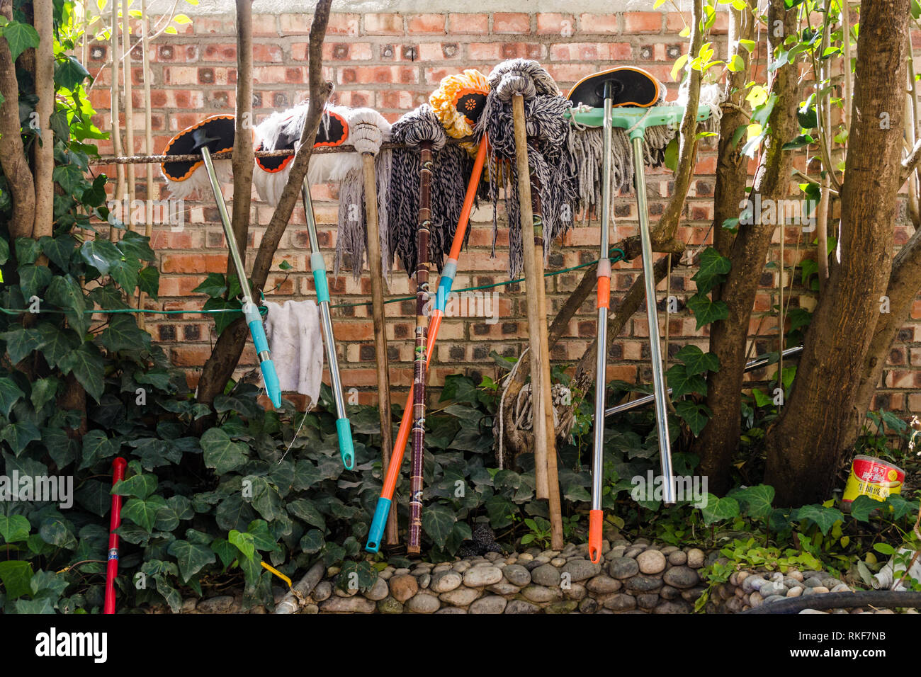 Brooms and mops hanging outdoor - Stock Image