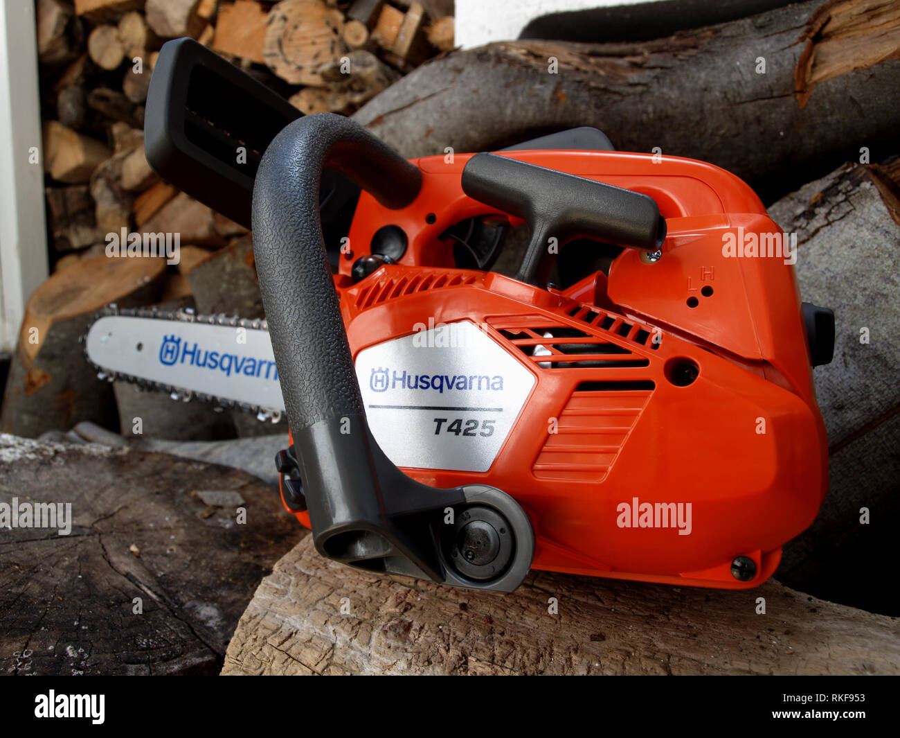 Brand new Husqvarna T425 Chain Saw on woodpile ready fro use - Stock Image