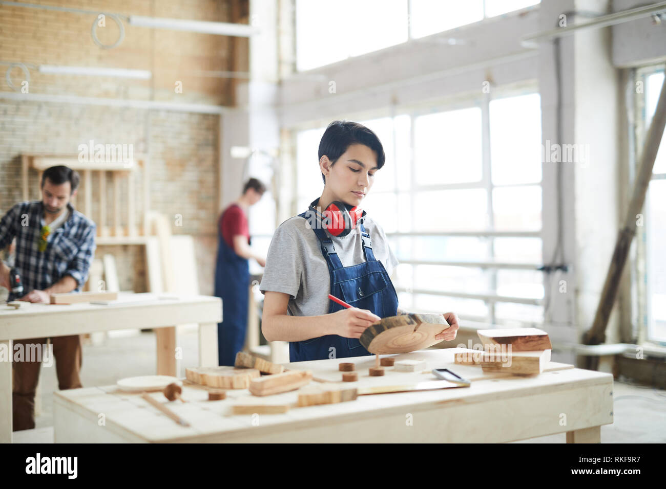 Masculine girl drawing on slice of wood Stock Photo