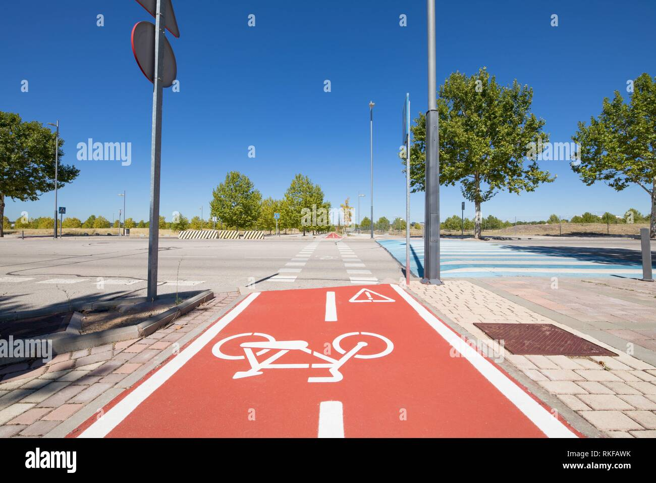 bike double red lane, with cycle symbol, and blue elevated crosswalk in urban street in Valdeluz town, near Guadalajara city, Spain, Europe. - Stock Image