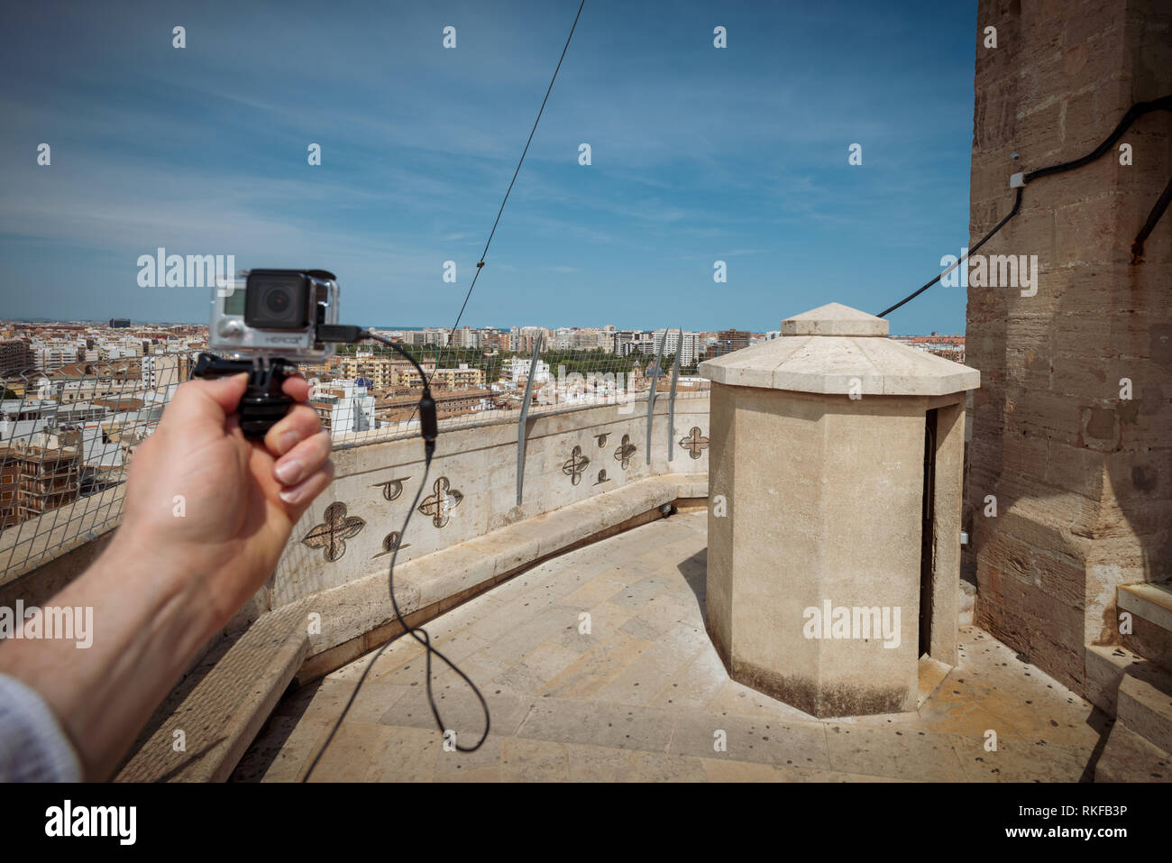A man holds a GoPro camera in front of the view across the city at the top of the El Miguelete, the bell tower of the Valencia Cathedral, in Valencia, Stock Photo