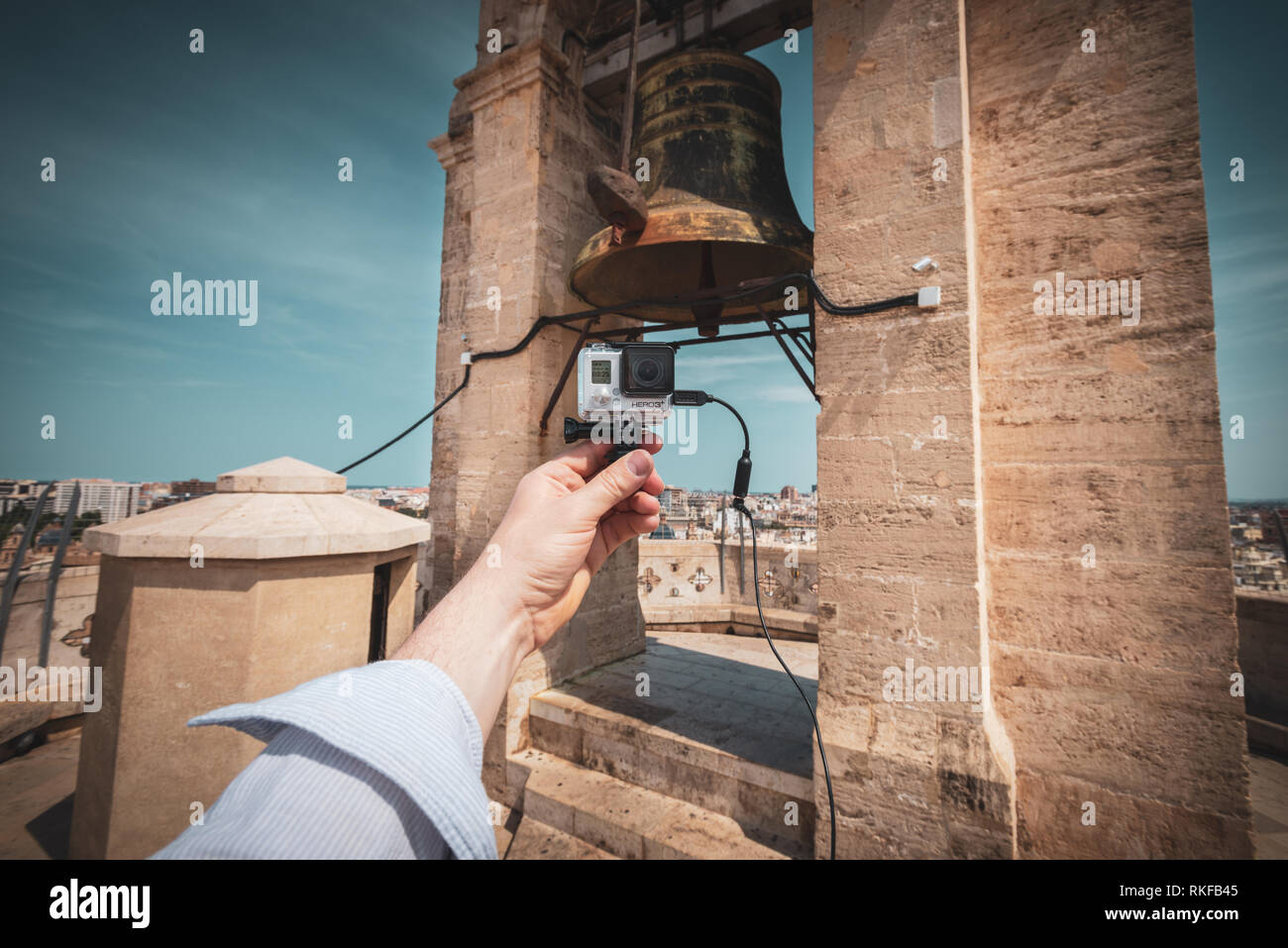 A man holds a GoPro camera in front of a large bell at the top of the El Miguelete, the bell tower of the Valencia Cathedral, in Valencia, Spain. Stock Photo