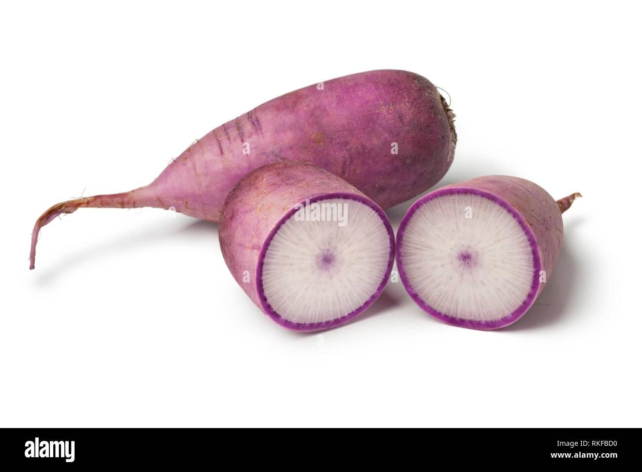 Fresh whole and half purple Japanese daikon radish on white background. - Stock Image