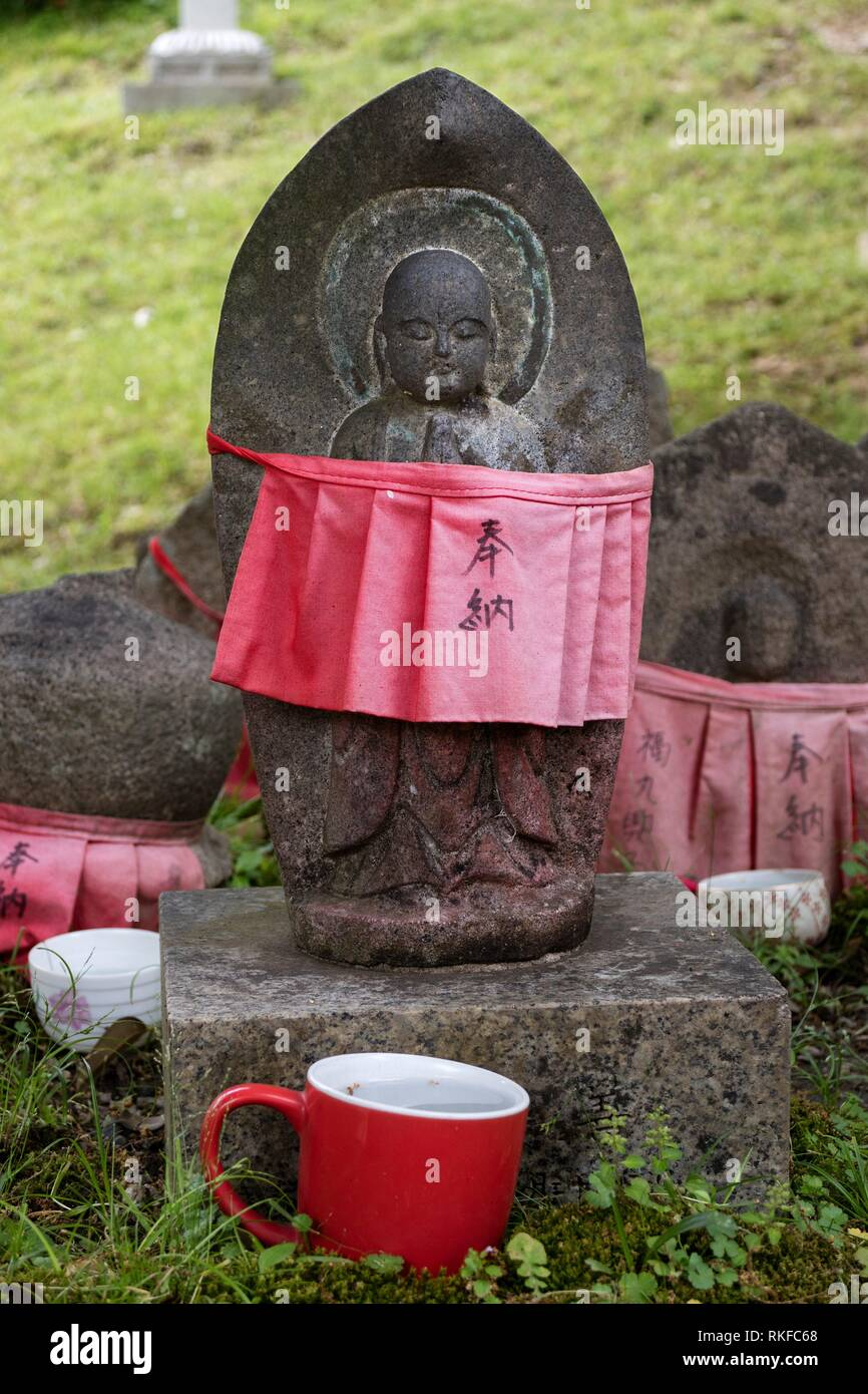 Traditional stone carved Jizo with red skirt honored and respected with a cup of water. - Stock Image