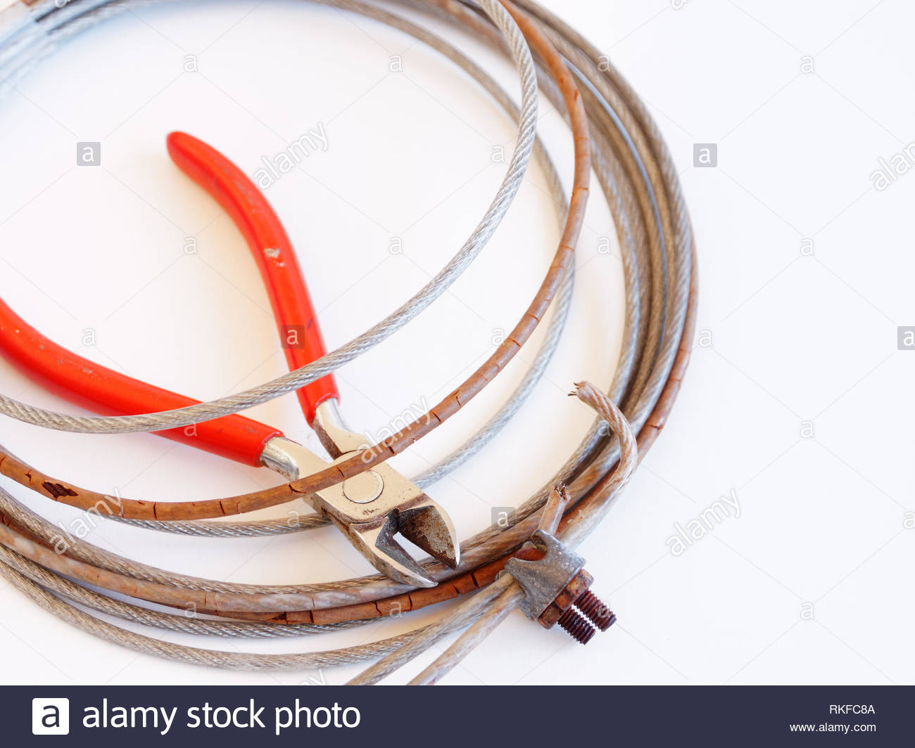 Old worn out plastic covered steel wire with wire cutters on white with copy space - Stock Image