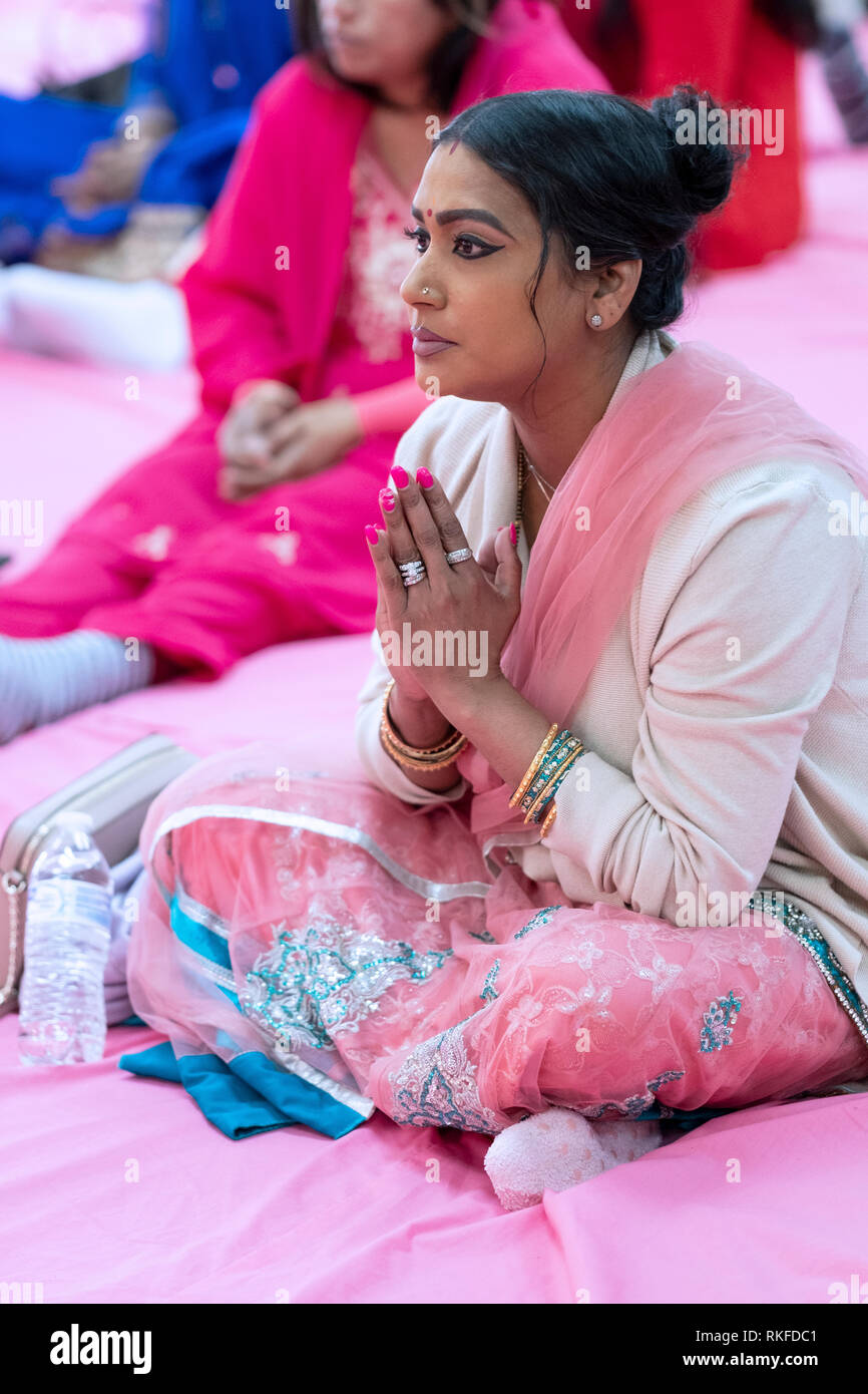 A beautiful striking Hindu woman sitting on the floor at morning prayers at a Hindu temple in Jamaica, Queens, New York City. - Stock Image