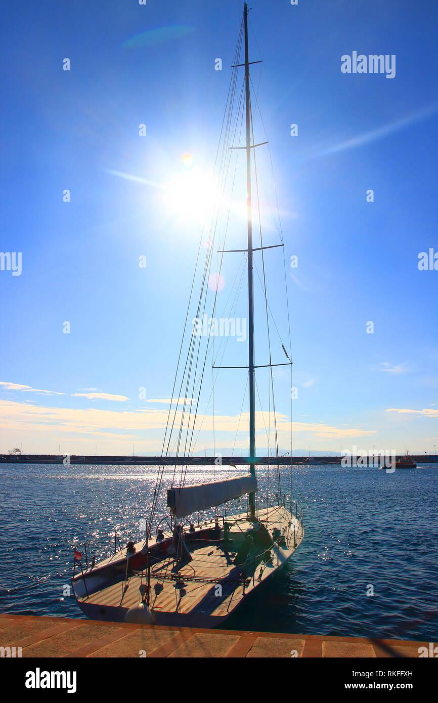 Sailing boat in prot of Rijeka, Croatia; sun on blue sky in background Stock Photo
