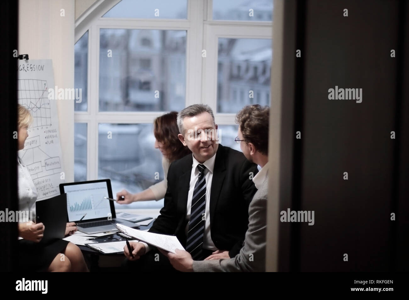 business partners engaged in dialogue in a modern office. - Stock Image