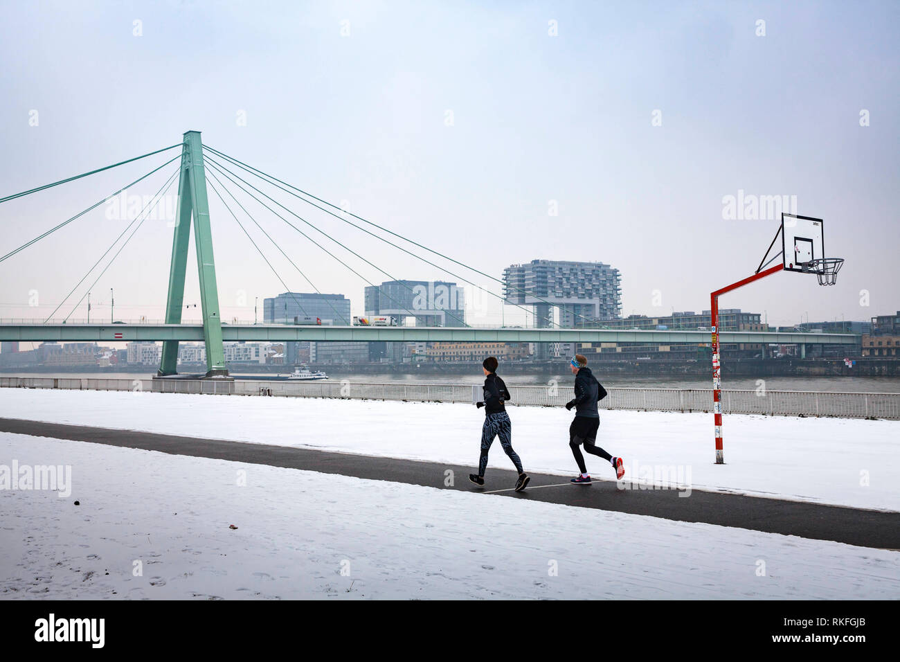 jogger on the Rhine riverbank in the district Deutz, the Severins bridge, in the background the Rheinau harbor, snow, winter, Cologne, Germany.  Jogge - Stock Image