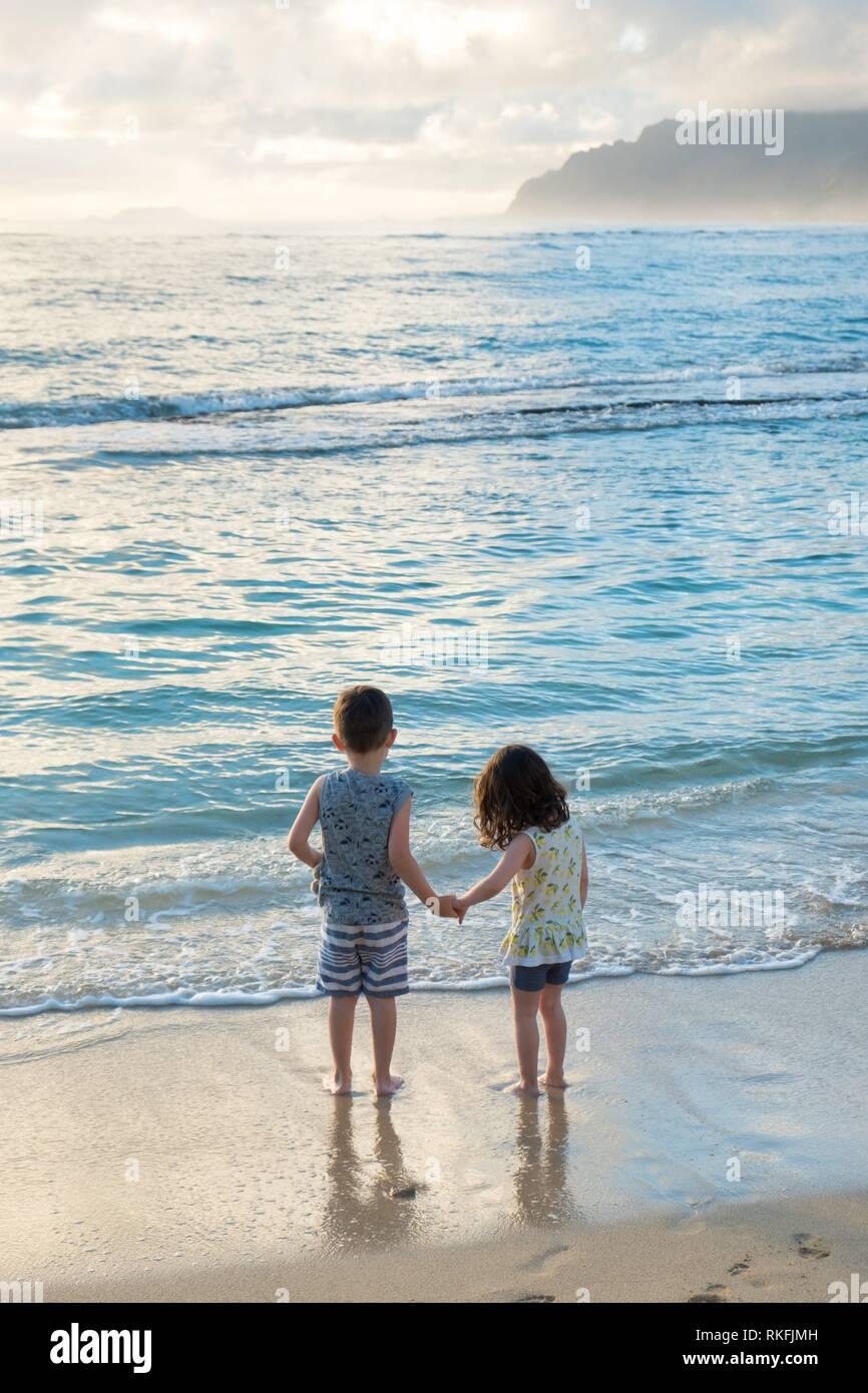 Siblings experiencing the beach and ocean together while on a tropical vacation to Oahu Hawaii with nice warm weather even at sunrise. Stock Photo