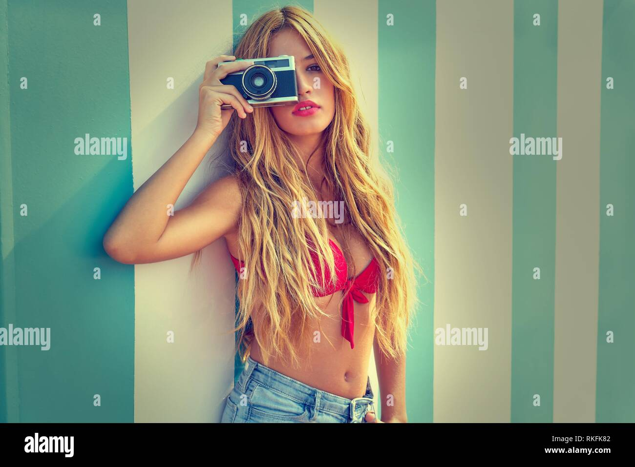 Blond teen summer girl with vintage photo camera in blue stripes wall background filtered image. - Stock Image