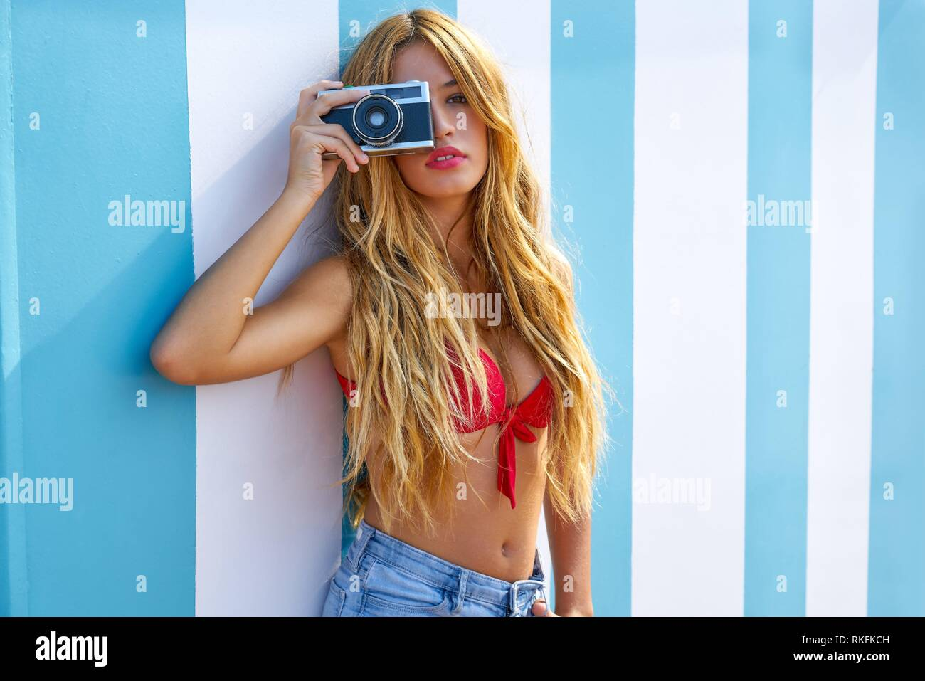 Blond teen summer girl with vintage photo camera in blue stripes wall background. - Stock Image