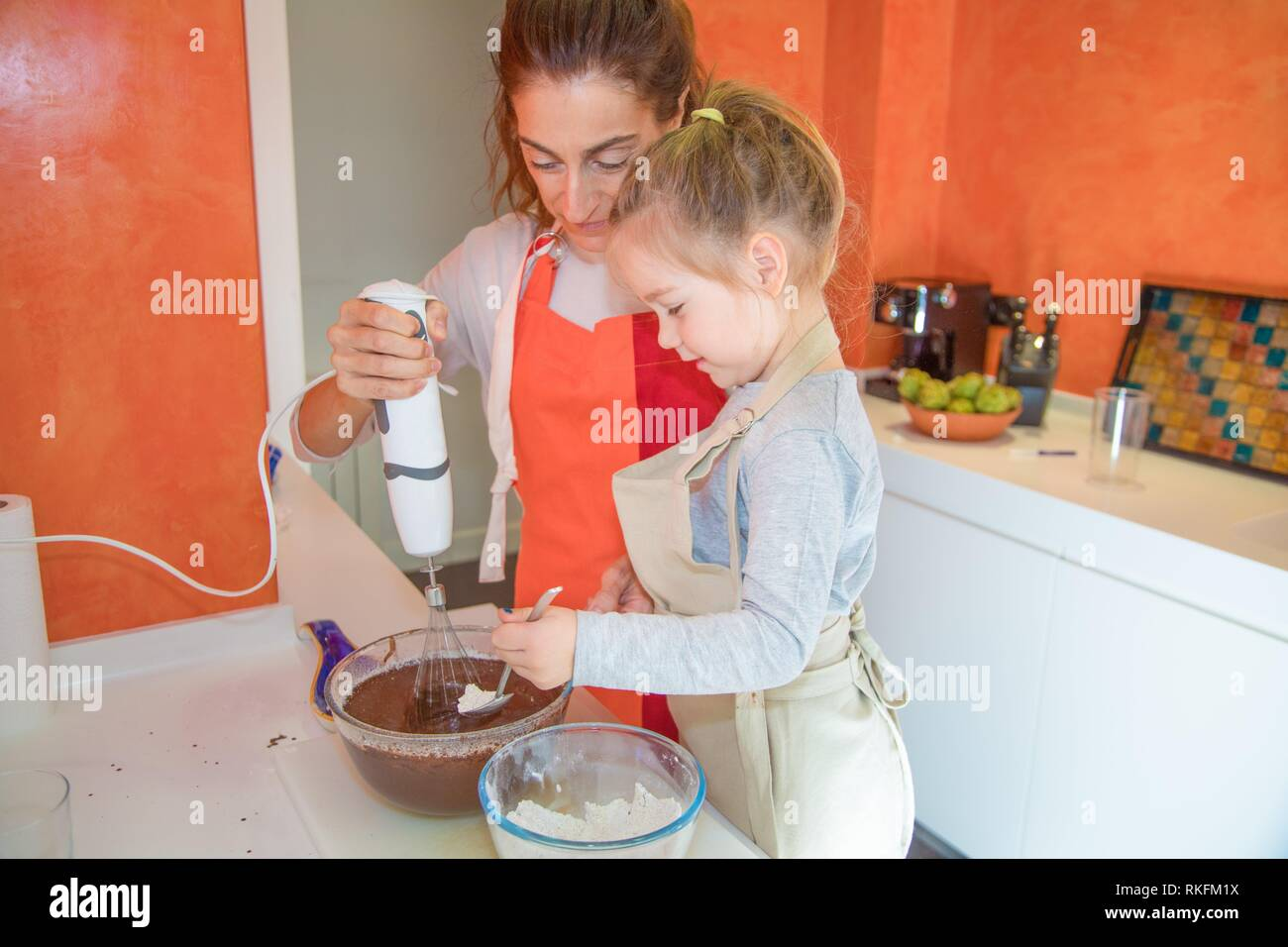 four years old girl pouring flour on chocolate cream and woman whisking with electric mixer in glass bowl, in teamwork, cooking a sponge cake at - Stock Image