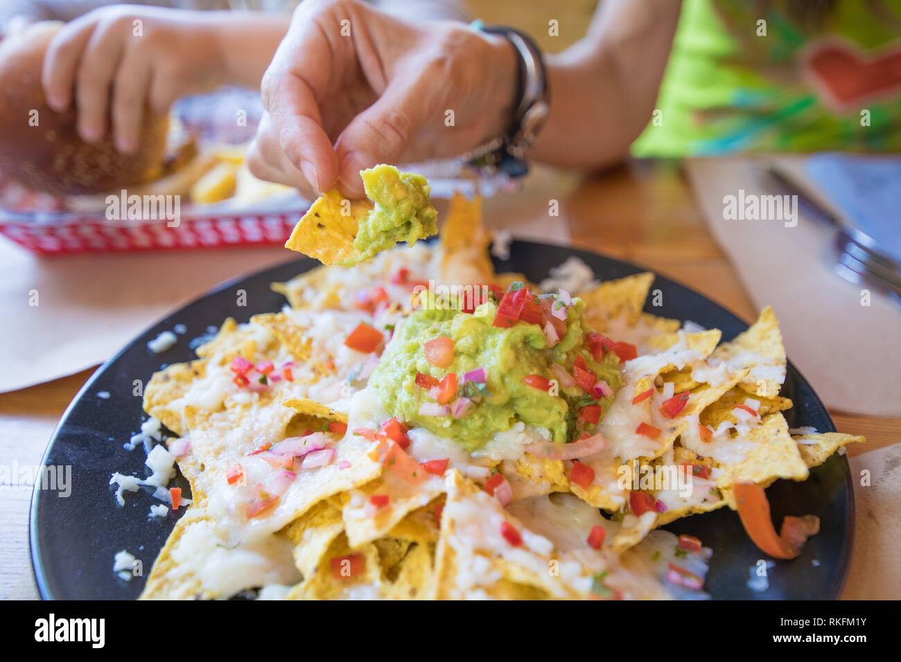 woman hand dipping nacho chips in avocado guacamole, cheese and chopped tomato on black plate, on wooden table with paper placemats at restaurant. Stock Photo