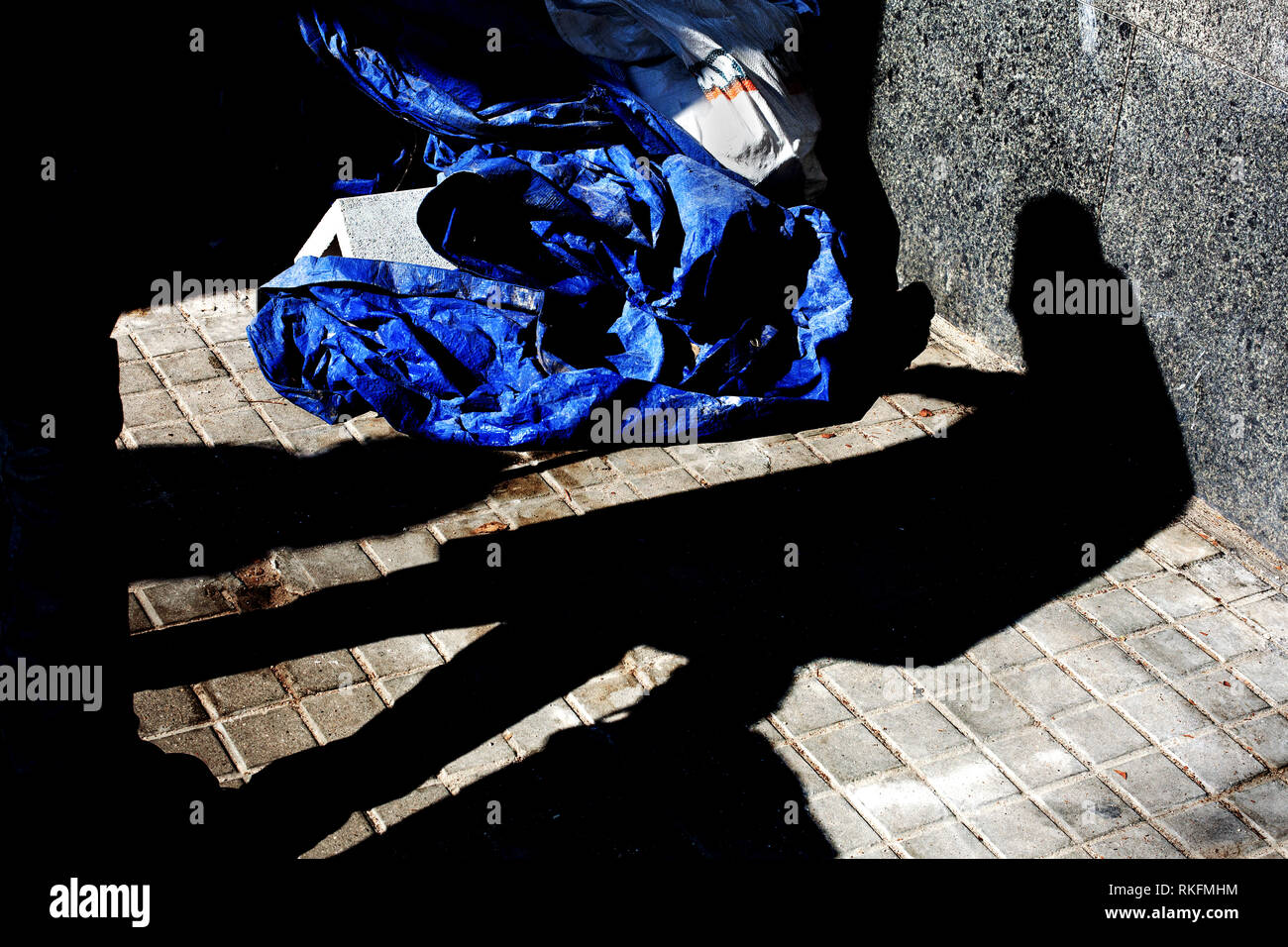Shadow of old, hunched man in the street. - Stock Image