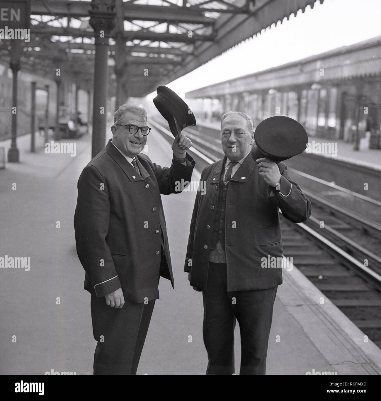 1968, two cheerful uniformed British Rail staff, a station foreman and ticket collector, standing on the platform at Blackheath railway station, raising their caps, Blackheath, London, England, UK. Stock Photo