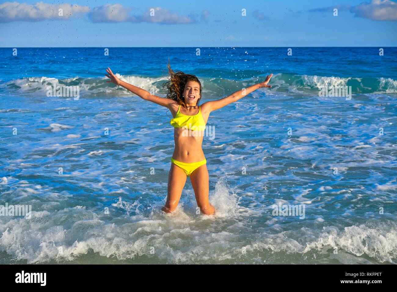 Bikini teen girl jumping happyt in Caribbean sunset beach splashing shore. - Stock Image