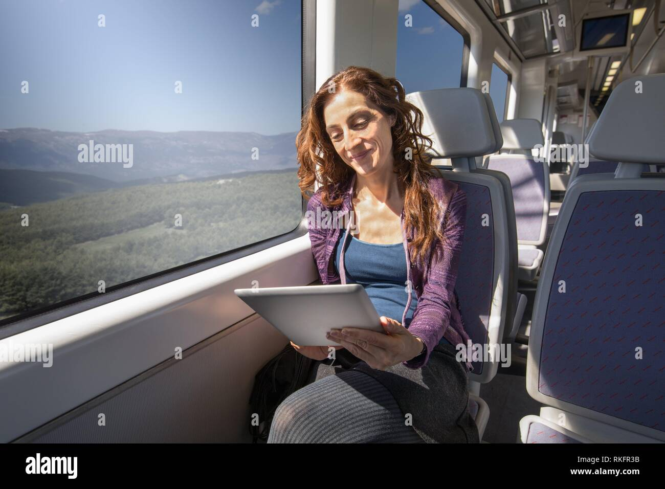 red hair smiling woman dressed in purple and blue, traveling by train sitting reading digital tablet or ebook. - Stock Image