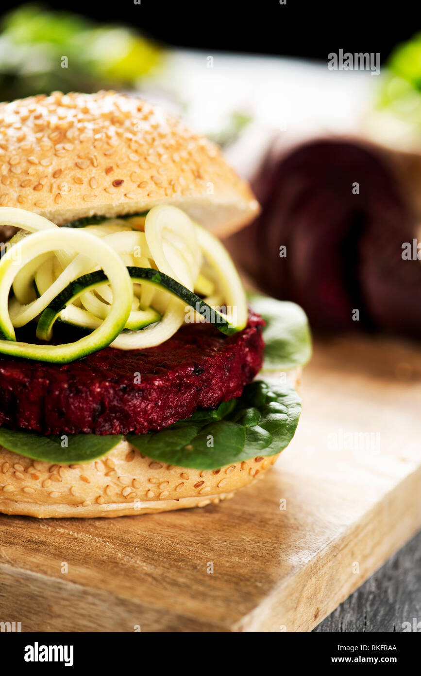 closeup of a beet burger sandwich, with some slices of zucchini, on a wooden table Stock Photo