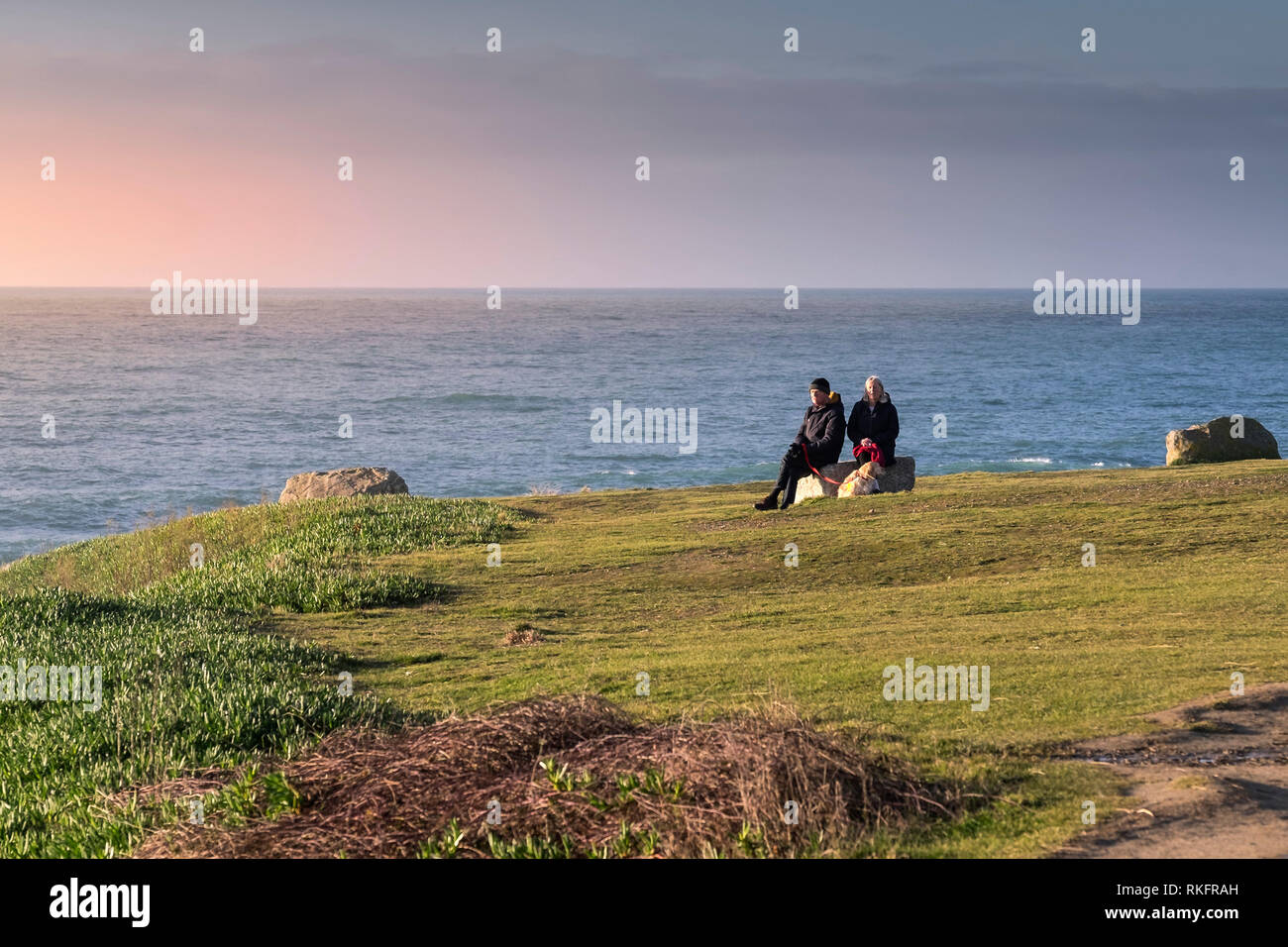 Two mature people and their pet dog sitting on a rock and enjoying the evening sunlight. - Stock Image