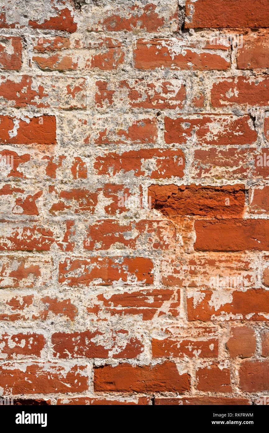 An old weathered, damaged, formerly painted, badly repaired red brick wall full frame background. Stock Photo