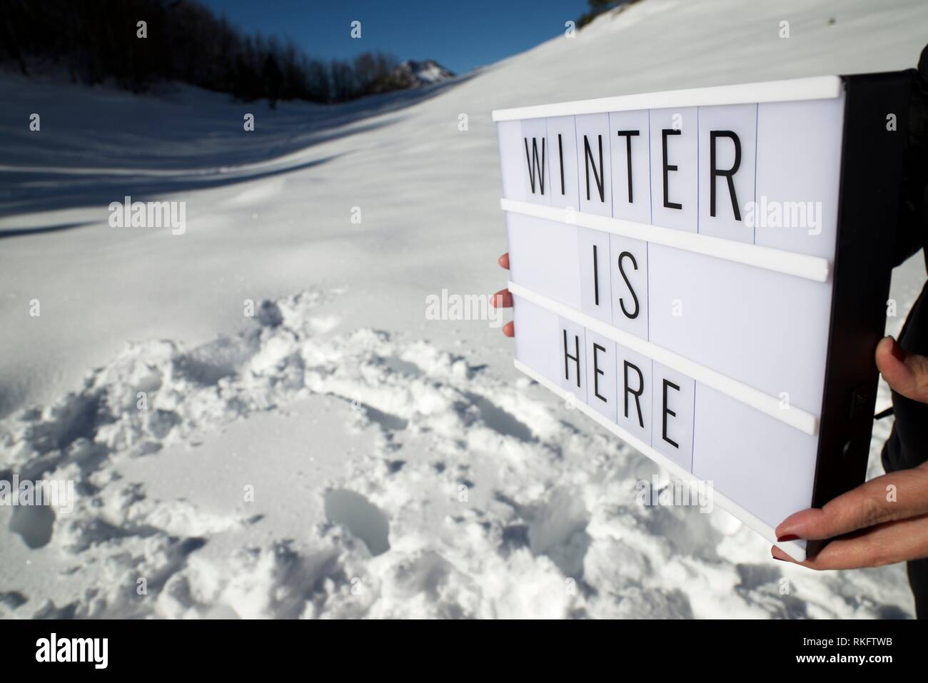 Slogan ''winter is here'' held by a woman in a snowy landscape. - Stock Image