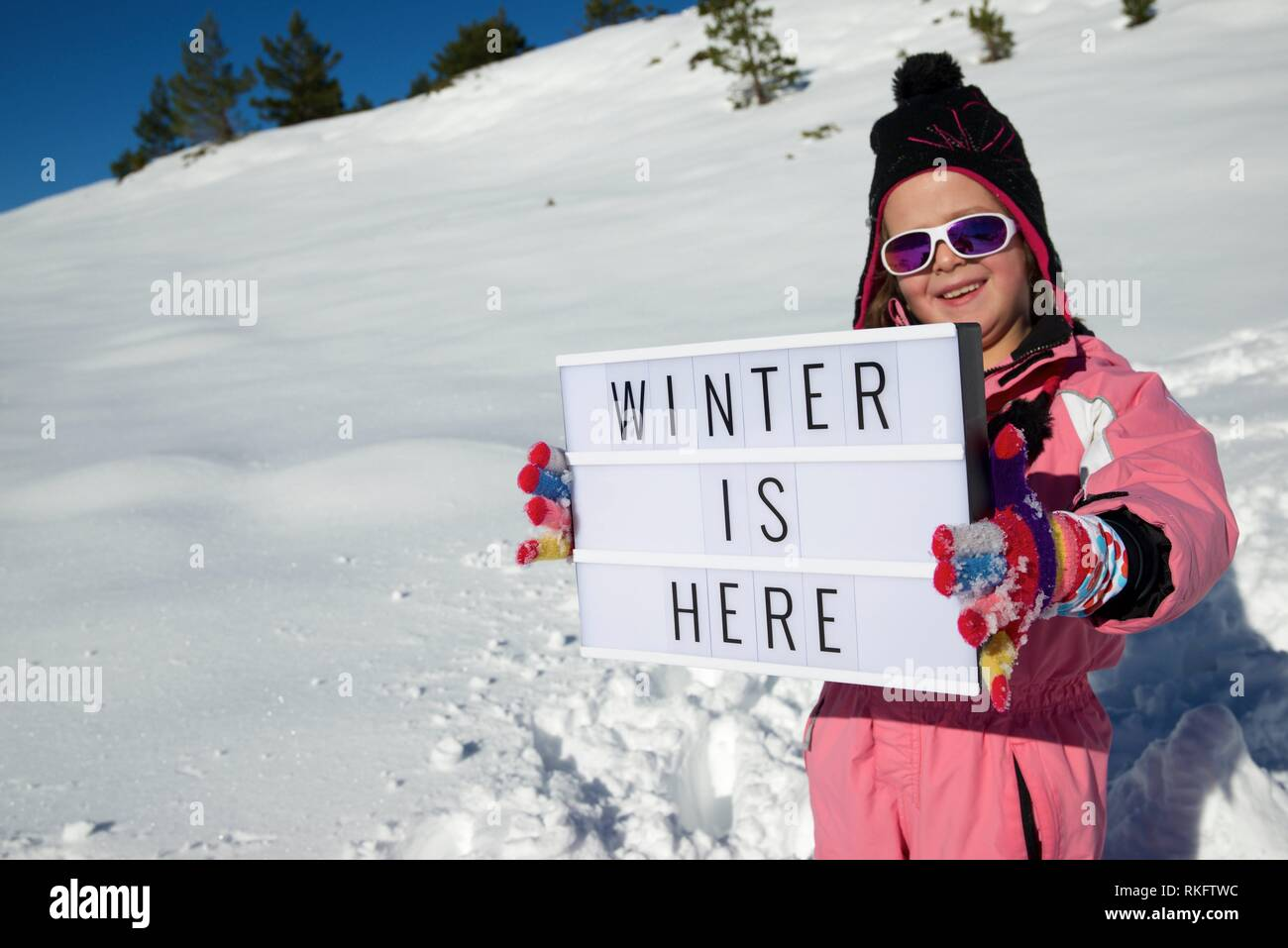 Slogan ''winter is here'' held by a girl in a snowy landscape. - Stock Image