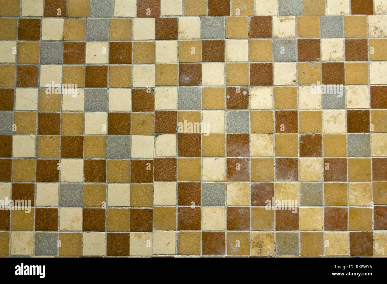 Old distressed floor tiles. Small size in fifties or sixties colours. - Stock Image