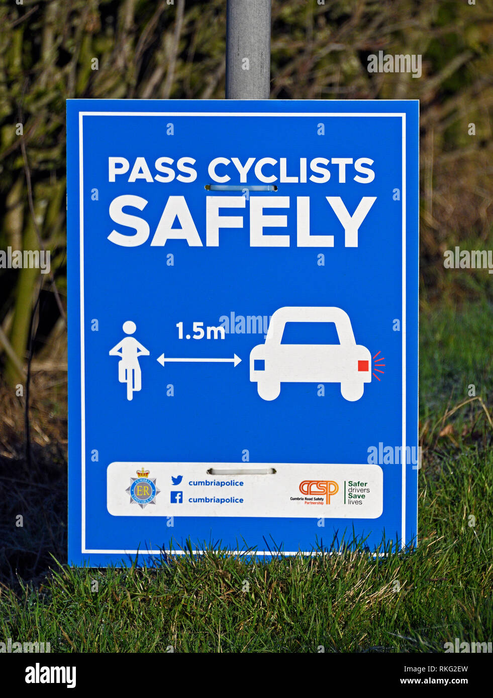 """Cumbria Police road safety notice. """"PASS CYCLISTS SAFELY"""". Hayclose Lane, Kendal, Cumbria, England, United Kingdom, Europe. Stock Photo"""