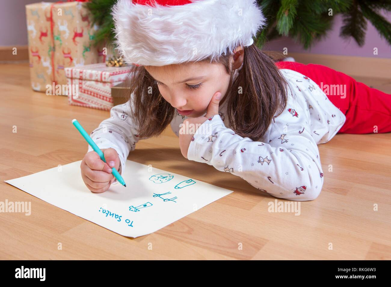 Little girl preparing The Santa Letter. She painting a sheet with header in English. Stock Photo