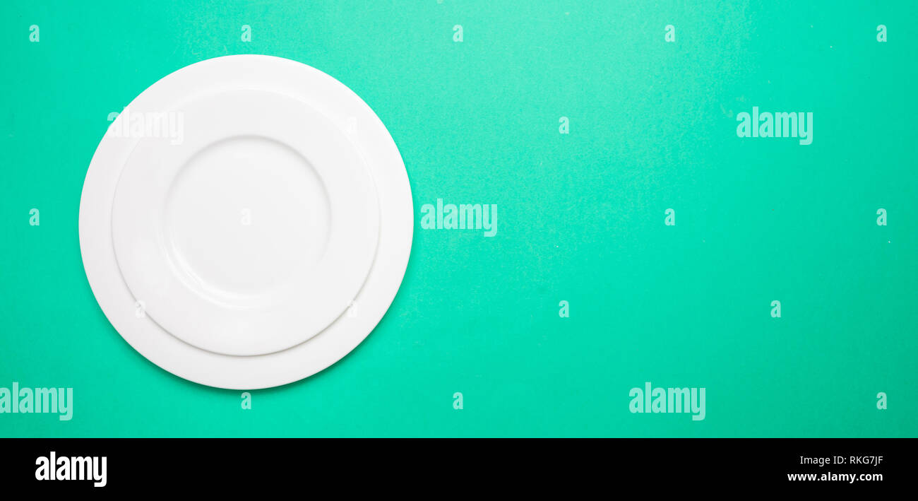 Set of empty white plates on green color background, banner, top view, copy space - Stock Image