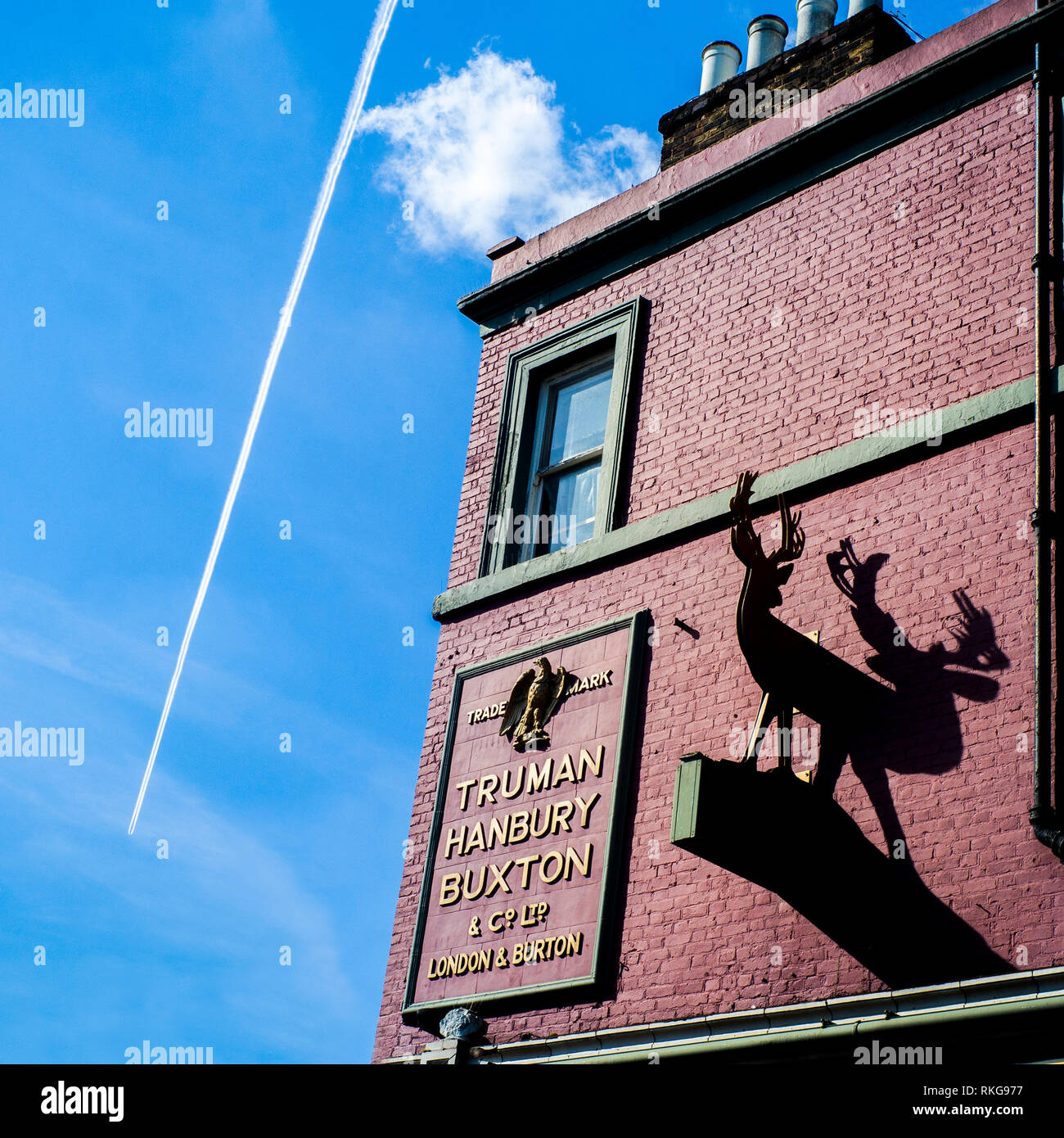 view of plane and vapour plume with pub in foreground, the bucks head pub external signage ,Camden, Truman Hanbury Buxton and Co ltd London Burton - Stock Image