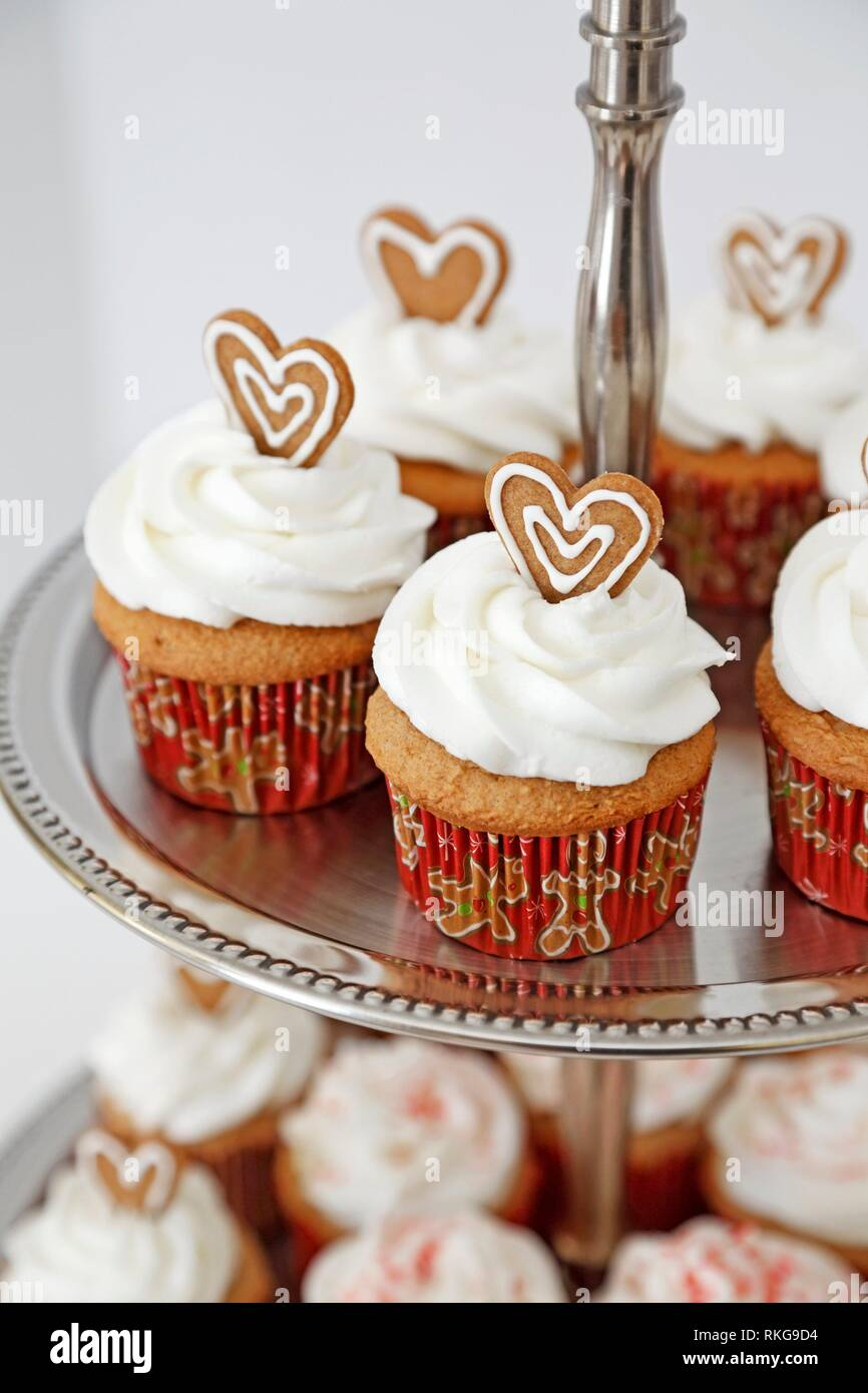 Cupcakes decorated with gingebread hearts in a two tier stand. - Stock Image