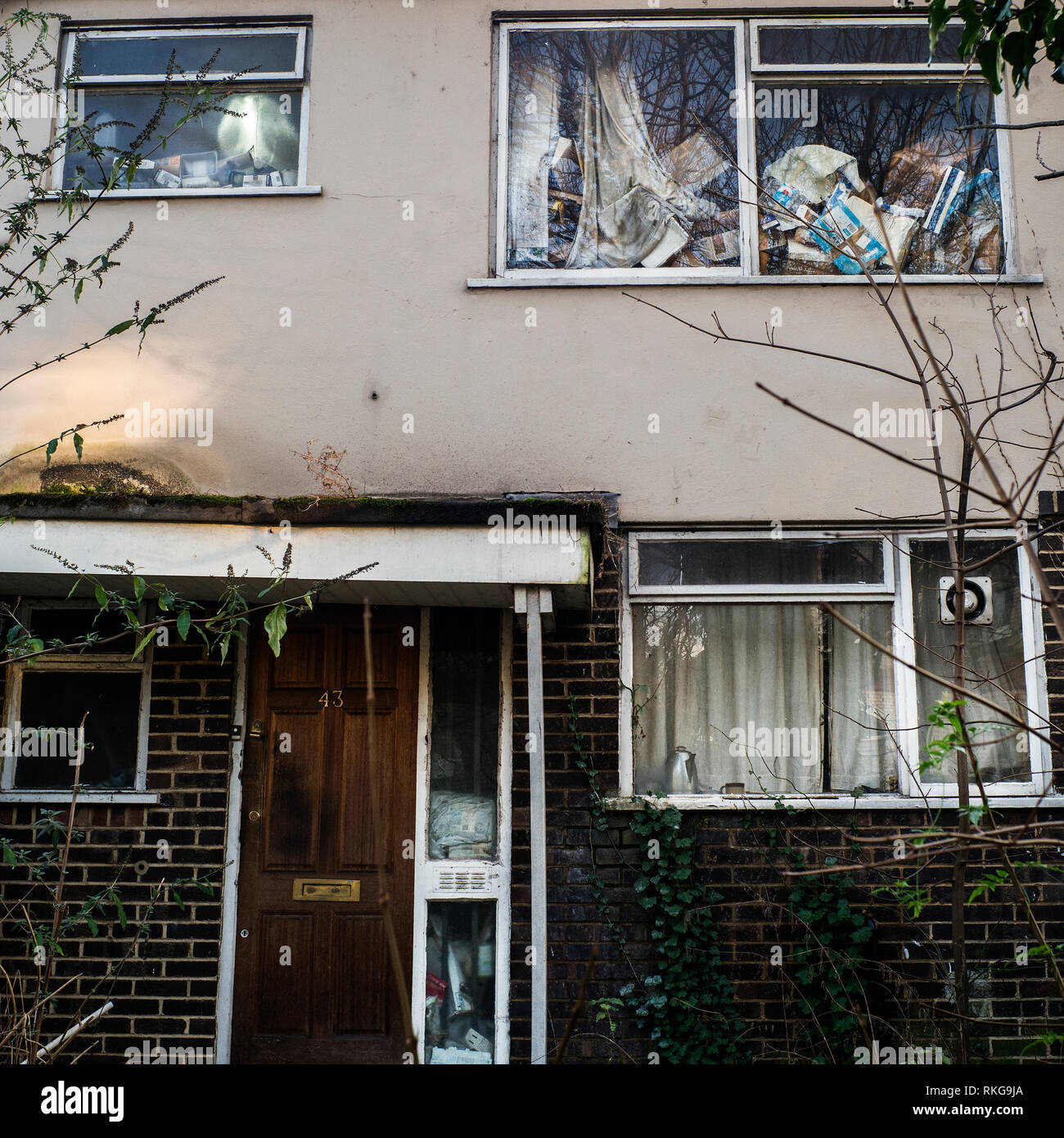 dilapidated house full of rubbish,inside house piled against window - Stock Image