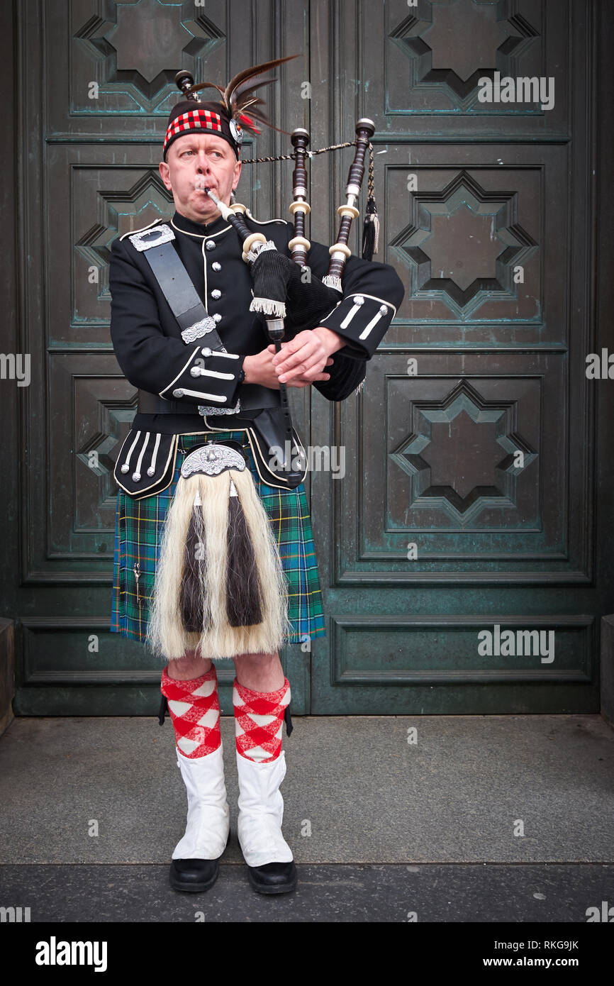 Edinburgh / Scotland - February 9th 2019: A man dressed in Scottish military uniform including kilt and sporran plays the bagpipes outdoors - Stock Image