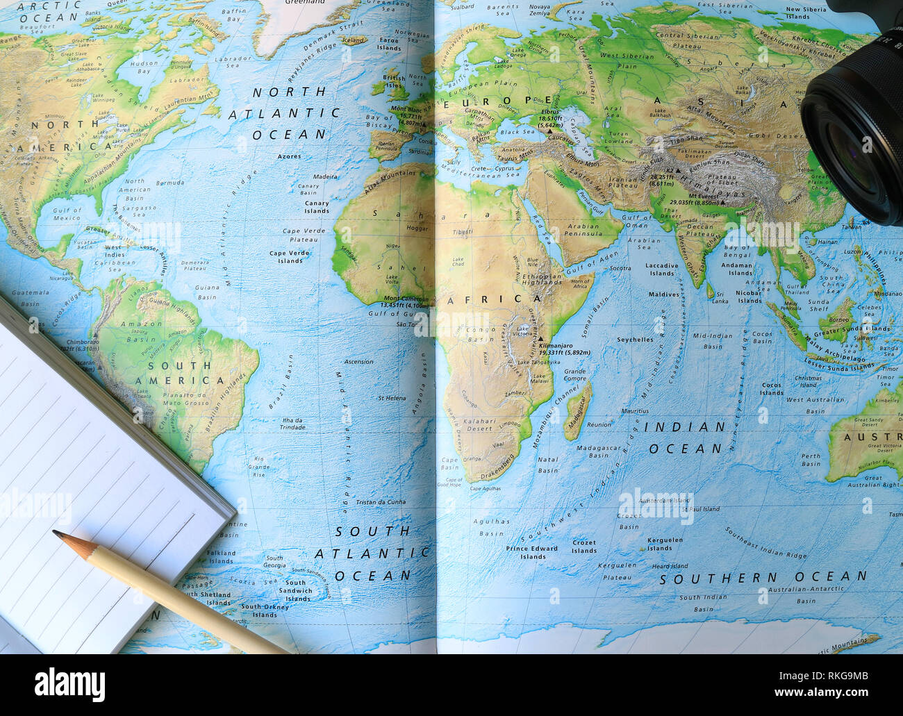 Lined Notebook with White Pencil and Camera on the World Map Stock Photo