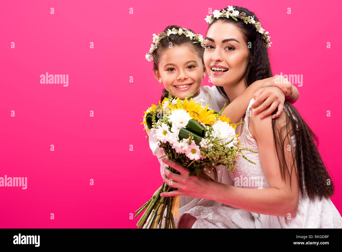 d525c8a09d beautiful happy mother and daughter with flower bouquet hugging and smiling  at camera isolated on pink