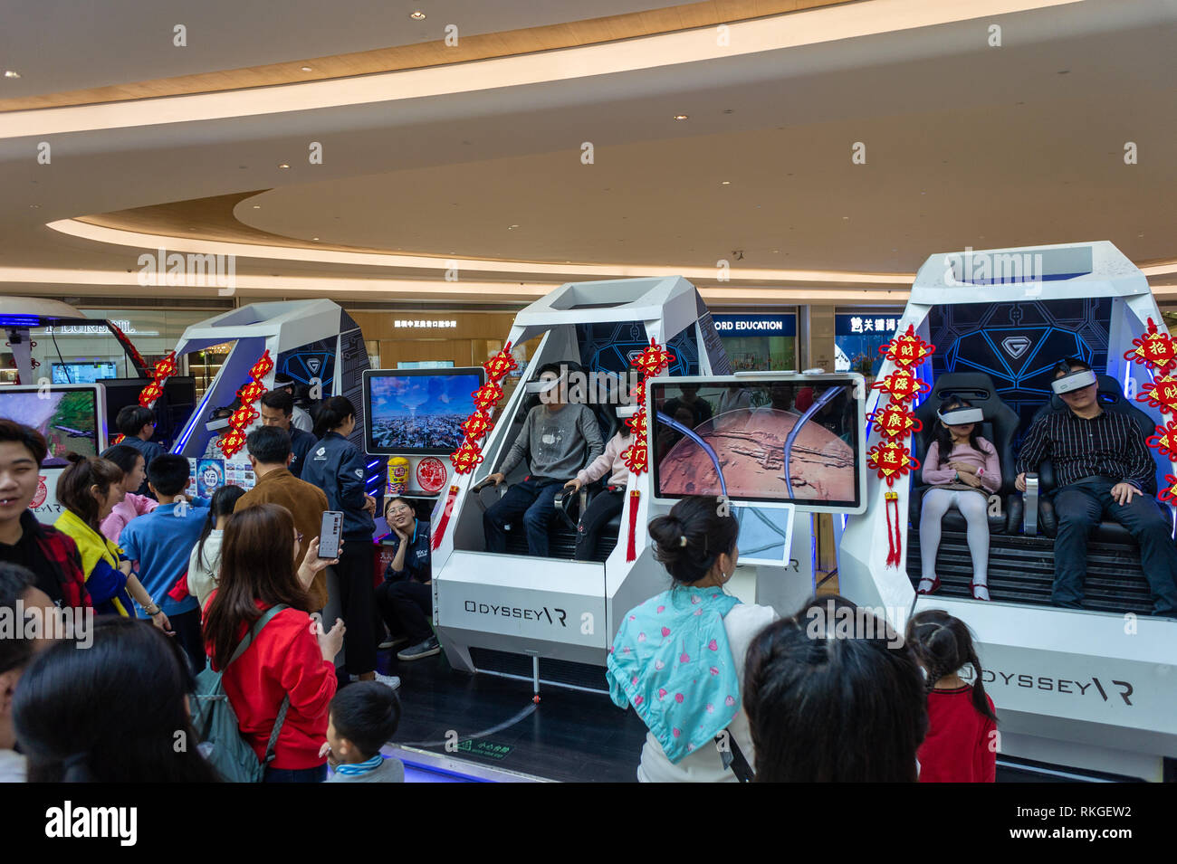 People enjoying VR games riding small space pods at a shopping mall